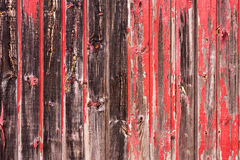 Red Painted Wood Paneling. An old worn barn or wooden fence with chipped red paint Royalty Free Stock Photos