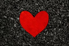 Red painted wooden heart on a grey stones background royalty free stock photos