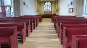 Red painted wooden pews stock image