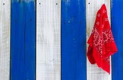 Red paisey bandanna hanging on wood door Stock Photos