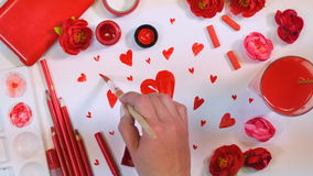 Red palette. Many hearts drawn on a paper. Artist desk from above. Valentines or Mothers Day concept. stock footage