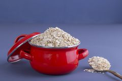 Red pan with dry oat flakes on gray background. Closeup. Concept healthy eating Stock Photos