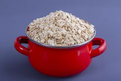 Red pan with dry oat flakes on gray background. Closeup. Concept healthy eating Stock Image