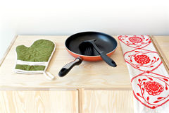 Red pan and green glove Royalty Free Stock Image