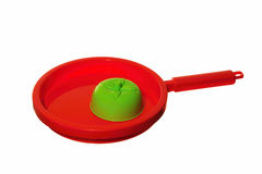 Red pan. Green tomato on a red pan - platick toys Stock Photo