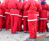 Red pants of people dressed as Santa Claus during the foot race Stock Photos