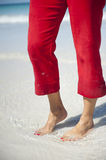 Red Pants and Toe Nails. Long female legs with red pants, bare feet with red toe nails, walking in the shallow water of a tropical beach Stock Images