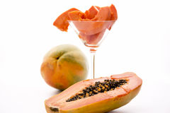 Red papaya for breakfast. The central cavity of a halved papaya in focus and behind it a glass filled with fruit pulp pieces Royalty Free Stock Photo