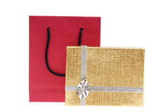 Red paper bag and gold gift box with bow Stock Photos
