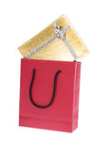 Red paper bag and gold gift box with bow Royalty Free Stock Photos
