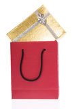 Red paper bag and gold gift box with bow Royalty Free Stock Photo