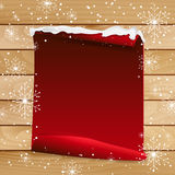 Red paper with bent corner on wooden background with snowflakes Stock Photography