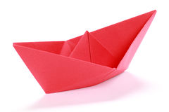 Red paper boat. Closeup of a red paper boat on white background stock photo