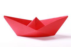 Red paper boat. Closeup of a red paper boat on white background stock images