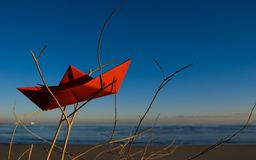 Red paper boat. Wrecked with blue aky in the background stock image