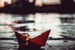 Red paper boat on fire. A paper ship burns on fire Royalty Free Stock Photography