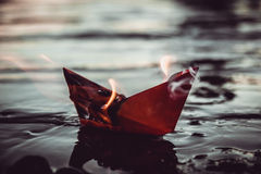 Red paper boat on fire. A paper ship burns on fire Royalty Free Stock Image