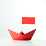 Red paper boat with flag. Origami red paper boat with flag on white background royalty free stock photography