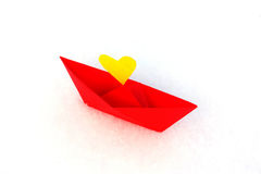Red paper boat with a heart in the snow Royalty Free Stock Photography