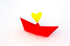 Red paper boat with a heart in the snow Stock Photo
