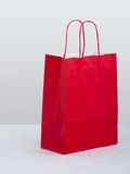 Red paper carrier bag, shopper on white tablecloth, table. Royalty Free Stock Photo
