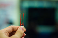 Red paper clip. Hand holding red paper clip on blurry background Stock Images