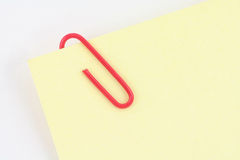 Red paper clip with yellow notepaper Royalty Free Stock Photos