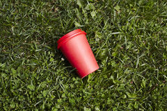 Red paper cup of coffee to takeaway on green grass lawn. Breakfast morning outside the cafe. Stock Image