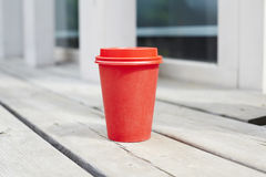 Red paper cup of coffee to takeaway on wooden floor outside the cafe. Breakfast morning on air. Royalty Free Stock Photography
