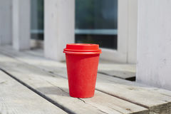 Red paper cup of coffee to takeaway on wooden floor outside the cafe. Breakfast morning on air. Royalty Free Stock Photos