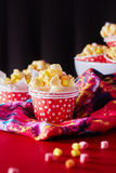 Red paper cup with popcorn against black background. Royalty Free Stock Photography