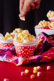 Red paper cup with popcorn against black background. Stock Photo
