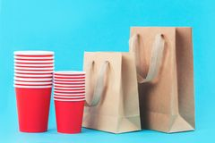 Red paper cups and eco bags on blue background royalty free stock photos