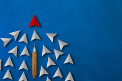 Red paper cut arrow as trend leader with many white arrows as fo Stock Images