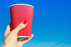 Red paper glass in female hand, background blue clear sky Royalty Free Stock Image