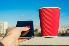 Red paper glass, phojne in female hand, background urban, blue clear sky Stock Images