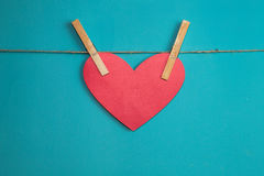 Red paper heart attached to a rope with wooden  pins Stock Image