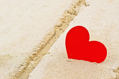 Red paper heart in beach sand Stock Images