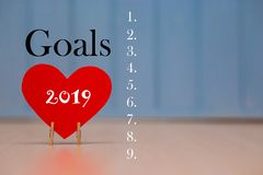 Red paper heart with 2019 goals list on blue wooden background, banner with copy space for text royalty free stock photos