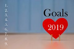 Red paper heart with 2019 goals list on blue wooden background, banner with copy space for text royalty free stock photo
