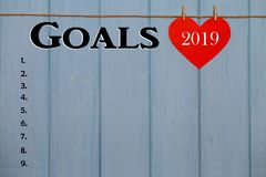 Red paper heart with 2019 goals list on blue wooden background, banner with copy space for text royalty free stock photography