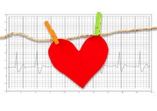 Red paper heart hanging on the clothesline on  electrocardiogram. Royalty Free Stock Photography