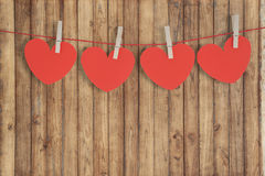 Red paper heart hanging on the clothesline on wood wall for valentine day Stock Image