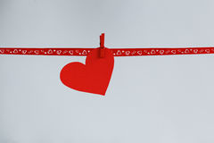 Red Paper heart hanging on red ribbon on background. Concept Valentines day Royalty Free Stock Image