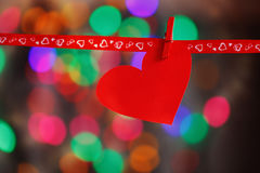 Red Paper heart hanging on red ribbon on colorful background. Concept Valentines day Stock Images