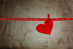 Red Paper heart hanging on red ribbon on grey background. Concept Valentines day Royalty Free Stock Image