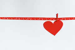 Red Paper heart hanging on red ribbon on white background. Concept Valentines day Royalty Free Stock Image