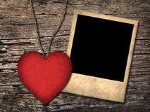 Red paper heart and old photo  on the wooden background Royalty Free Stock Photo