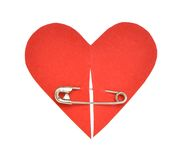 Red paper heart shape. Metal safety pin clip on paper heart Royalty Free Stock Images