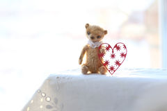 Red paper heart and the small brown toy bear made of wool sitting on a white napkin. warm colors. soft focus. Stock Photo